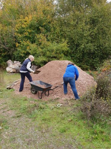 Jenny and Claire loading a wheelbarrow with Type 1 stone on November 2018's Task Day